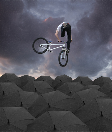 acrobat on a bicycle in the rain Stock Photo