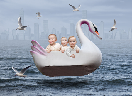Three boys in a swan boat on the sea