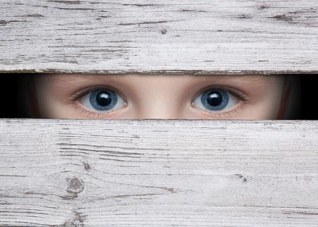 felicity: little boy looking between the gap of the boards