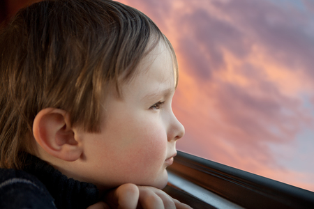 small child looks through a  window Stock Photo