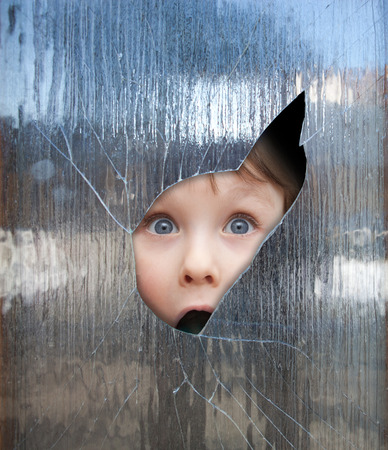 boy looks through a broken window Stock Photo