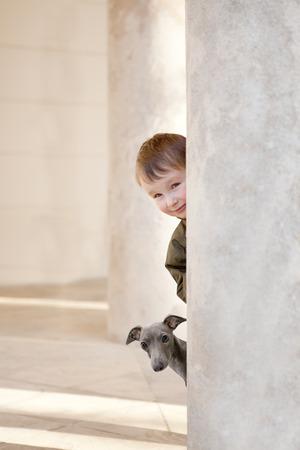little boy hiding behind a pillar Stock Photo