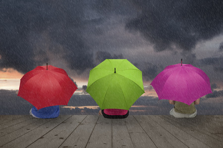 Three people are hiding under umbrellas against the rain Stock Photo