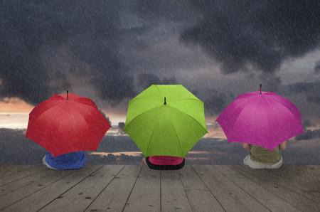 Three people are hiding under umbrellas against the rain Stock Photo