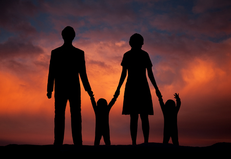 Family of parents and two children watching sunset Stock Photo