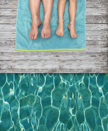 Two people resting on a towel by the pool