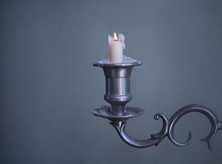 old candlestick with burning wax candle