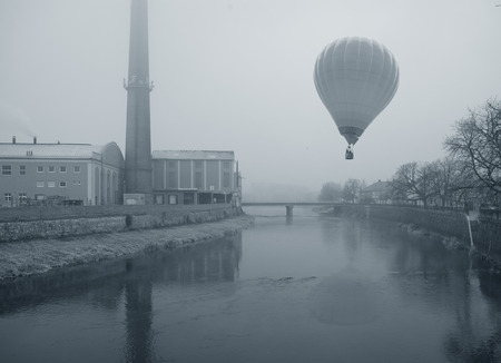 monochromatic photo of a hot air balloon flying in the fog over the city