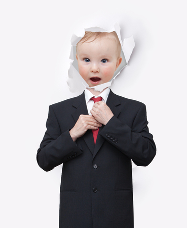 Picture the face of a little boy in a paper hole and black suit