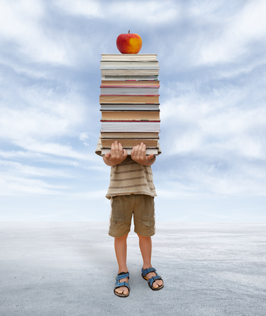 little boy is hiding behind a pile of books and apple Stock Photo
