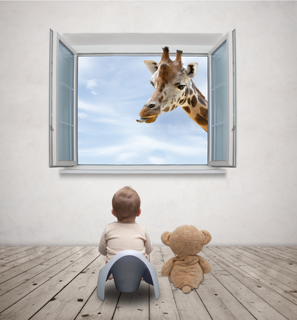 baby on the potty watching giraffe Stock Photo