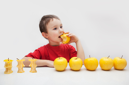 Boy eating yellow apple Stock Photo