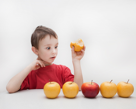 little boy eating yellow and red apple Stock Photo