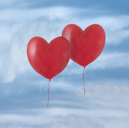 Two red balloons flying in the sky