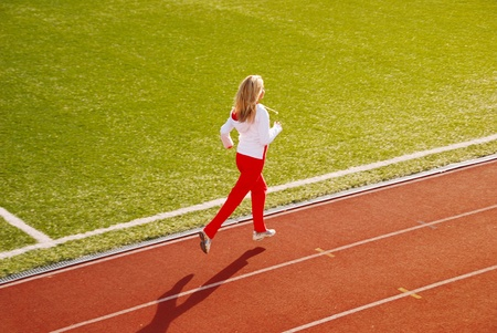 Teenage girl jogging on stadium Stock Photo - 12238287