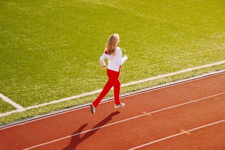 Teenage girl jogging on stadium