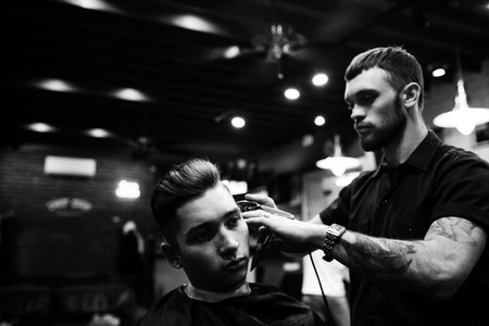 sideburns: Man at the hairdresser. Portrait of a young white boy while cutting hair in the hair salon Stock Photo