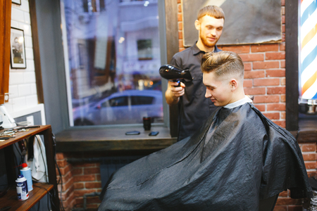 shearer: Man at the hairdresser. Portrait of a young white boy while cutting hair in the hair salon Stock Photo