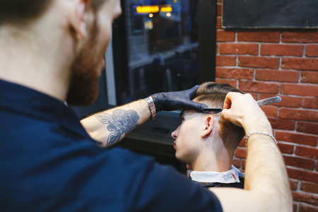 straight man: Hairdresser shaving young man with a straight razor