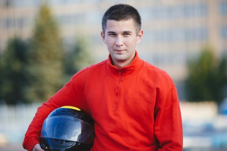 motorizado: Race driver portrait, handsome man wearing sportive outfit and stylish sunglasses, holding helmet, happy winner of a race, active lifestyle concept