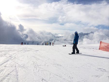 piste: Panoramic view of snowboarder on snowy slope with new fallen snow. Caucasus Mountains, Georgia, region Gudauri.