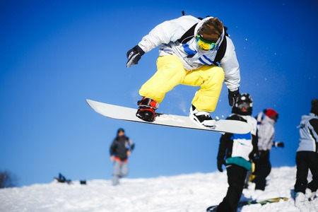 Snowboarder jump from wooden springboard in the mountains Stock Photo