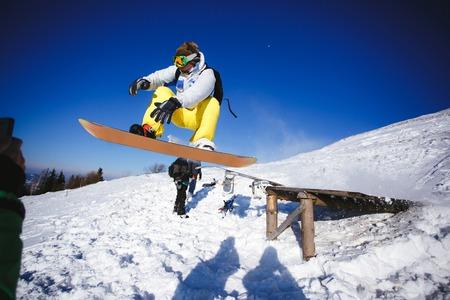 Snowboarder salto de trampolín de madera en las montañas