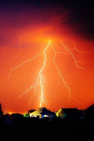 Cloud to Ground Electric Lightning behind house roof tops.