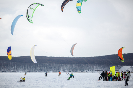 snowkiting: snow kiting on a snowboard on a frozen lake.