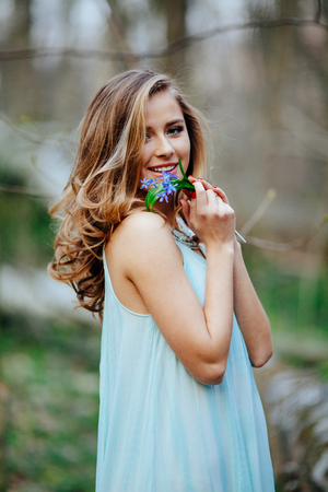 Beautiful girl attractive model in blue dress smell and enjoy fragrance of snowdrop flowers in the spring forest.