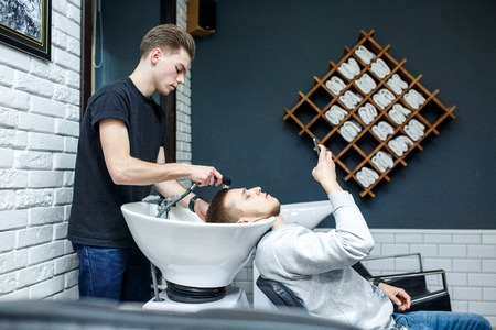 A hairdresser man washes hair head to the client in the chair Stock Photo