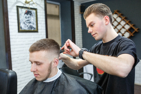 scissors: Great time at barbershop. Cheerful young bearded man getting haircut by hairdresser while sitting in chair at barbershop.