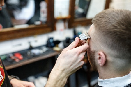 comb: Great time at barbershop. Cheerful young bearded man getting haircut by hairdresser while sitting in chair at barbershop.