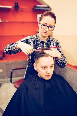 young attractive woman hairdresser make hairstyle for man.
