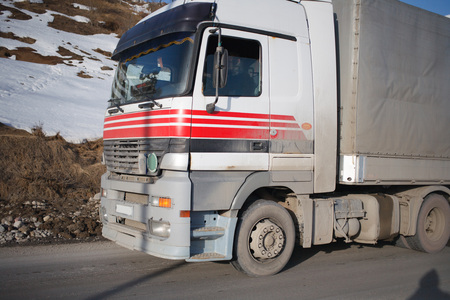 truck driver: White refrigerated truck on winter road on background of the mountains.
