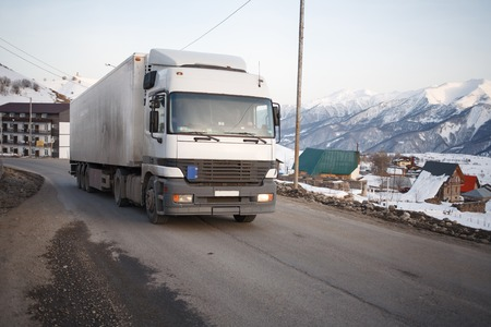 White refrigerated truck on winter road on background of the mountains.