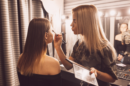 make up artist doing professional make up of young woman. Banco de Imagens