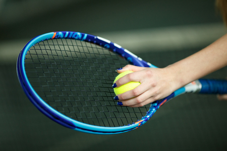 Players hand with tennis ball preparing to serve.