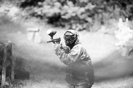 gunfire: Paintball sport player in uniform and mask with gun outdoors