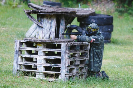 gunfire: Paintball sport player in uniform and mask with gun outdoors. Stock Photo