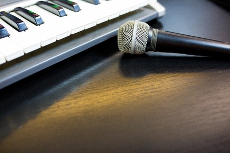 Image of keyboard with microphone on black background Stock Photo