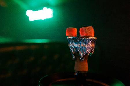 Hookah hot coals on shisha bowl with mouthpieces and color lights Stock Photo