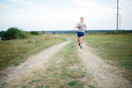 Sport and fitness runner man doing outdoors training for marathon run. Guy doing high intensity interval training sprint workout along lake in summer. Male athlete sports model fit and healthy aspirations. Reklamní fotografie