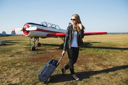 Beautiful woman in black leather jacket standing in front of small vintage aircraft. 写真素材