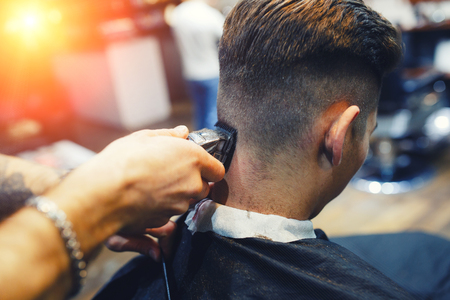 Man in the barbershop. Close up of a young white guy while hairstylist cutting hair in the hairdressing salon. Close up back view. Stock Photo