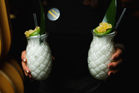 Waiter carries two white cocktails