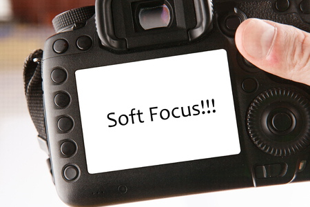 Back side of professional dslr digital photo camera with text soft focus on screen. Close-up view of LCD screen and viewfinder with control buttons. Blurred background