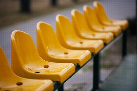 Empty yellow seats on the sport stadium. Imagens