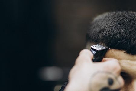 Coiffeur faisant des cheveux dans le salon de coiffure avec tondeuse