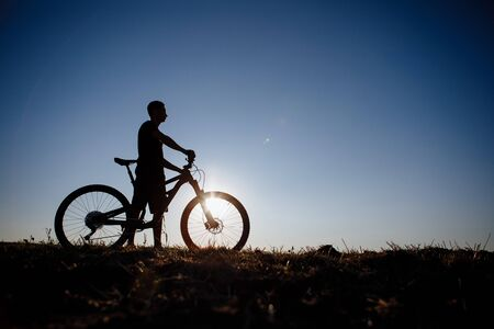 The silhouette of a bicycle and rider against the blue sky at sunset. Stock Photo